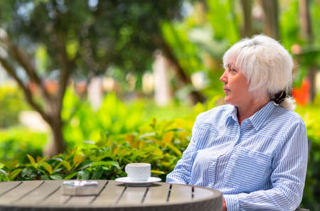 Attractive middle-aged woman relaxing on an outdoor patio surrounded with lush green plants enjoying a cup of coffee or tea