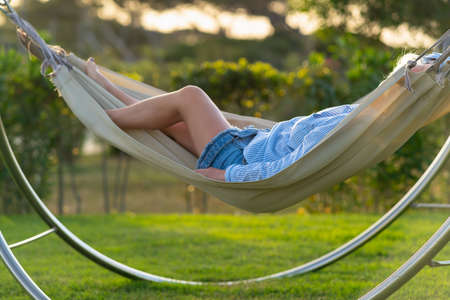 Unrecognisable woman relaxing in a hammock at sunset on the green lawn of a garden or park in a close up view backlit by the warm glow of the sun