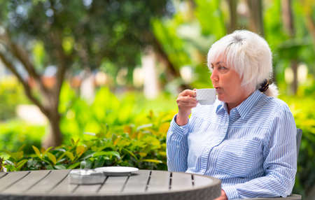 Thoughtful woman relaxing with a cup of tea or coffee on an outdoor patio with lush green tropical plants in a close up view across the table