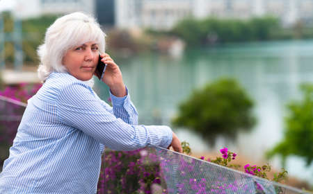 Woman looking thoughtfully at camera as she chats on a mobile phone while leaning on the glass balustrade of an outdoor patio overlooking water