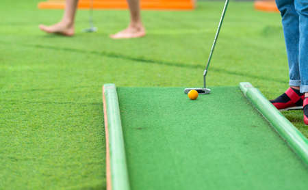Person teeing off at a game of miniature golf or minigolf on an artificial outdoor course in a low angle view of the ball and club