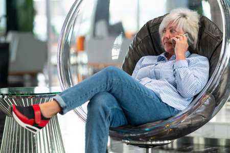 Middle-aged woman relaxing in a comfortable modern tub chair chatting on the mobile phone listening to the conversation with a thoughtful expression
