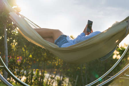 Woman lying relaxing on a hammock in the garden backlit by the evening sun with lens flare watching media or reading a message on her mobile phone