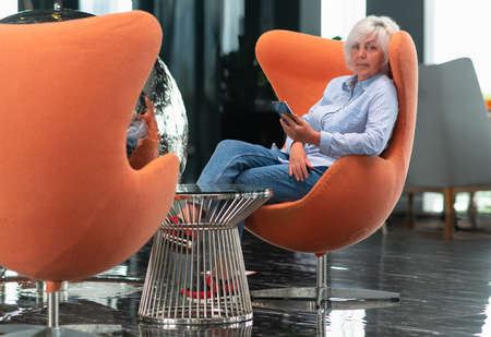 Middle-aged woman turning and looking thoughtfully at the camera as she relaxes in a comfy modern tub chair in a vestibule with her mobile phone