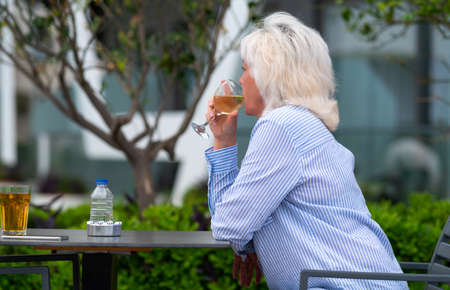 Woman sitting quietly sipping a glass of white wine outdoors at a table as she enjoys a relaxing day in a close up low angle upper body side view with copyspace 스톡 콘텐츠