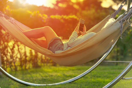 Woman relaxing at sunset on a hammock in a garden or park in a close up side view as she reads a message on her mobile phone backlit by the warm light of the sun