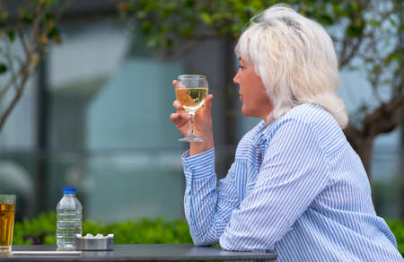 Woman enjoying a white wine aperitif at an outdoor restaurant table as she sits looking thoughtfully off to the side with copyspace