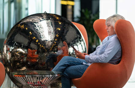 Woman relaxing in a comfy orange tub chair with her mobile phone reflected in a metallic silver circular orb sculpture alongside in a close up profile view