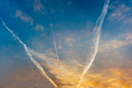 three tracks from an airplane in the sky move to the sunset