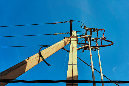 Electric pole with wiring against sky background