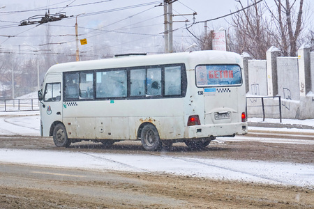 Rostov-on-Don / Russia - January 2018: A small Hyundai bus rides along route number 21 through the streets of a big city in winter