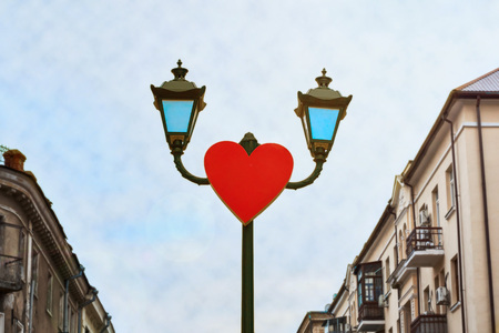 Red heart on a lamppost high above the path in the city Stock Photo