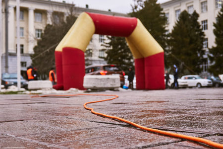 The inflatable arch of red and orange color is used for start of auto racing and receives electricity on an orange wire