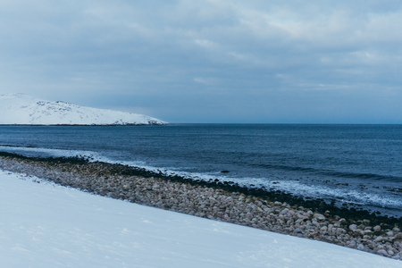 Rocky coast of the Arctic Ocean in the snow in winter while traveling Stock Photo