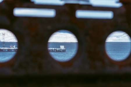 View of the winter ocean covered with snow through a rusty fence with a hole