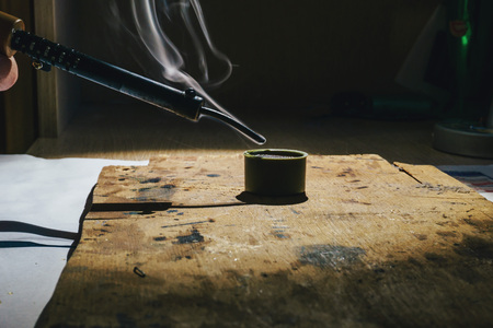 Working with a hot metal soldering iron at home under the spotlight and smoke that comes from liquid rosin 写真素材