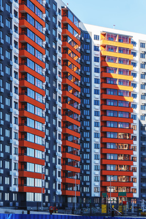 A multi-storey residential building painted in different colors against the blue sky, a freshly constructed one is waiting for new tenants to enter it