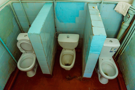 Old public toilet with three toilet bowls and red painted floor