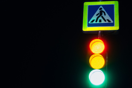 A traffic light at night shines with its lights and regulates a dangerous evening traffic