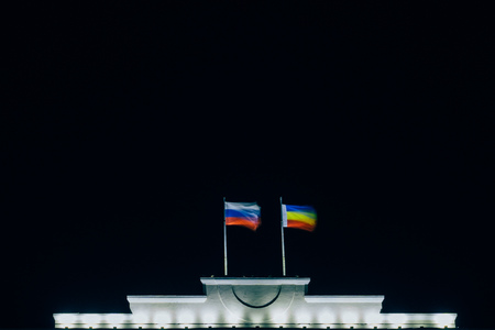 Flag of Russia and the Rostov region on the top of the building develop at night