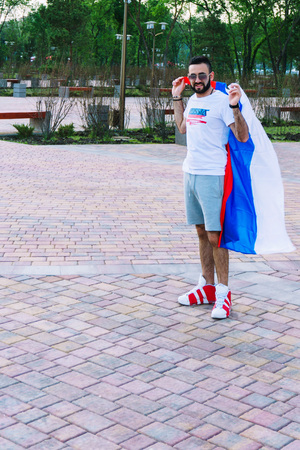A young guy with a beard in his white T-shirt and shorts is holding a flag of Russia that is developing in the wind