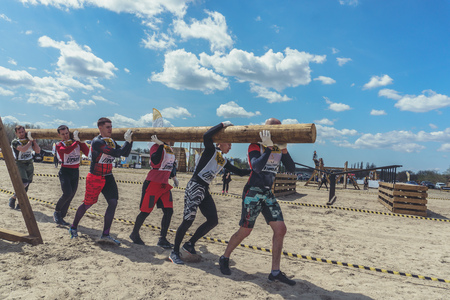 Rostov-on-Don / Russia - April 2018: Organized team run with obstacles in rough terrain with wooden structures on sand 報道画像