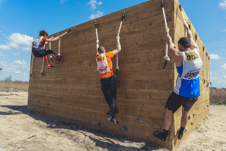 Rostov-on-Don / Russia - April 2018: Organized team run with obstacles in rough terrain with wooden structures on sand Editorial