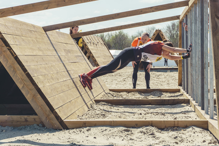 Rostov-on-Don / Russia - April 2018: Organized team run with obstacles in rough terrain with wooden structures on sand