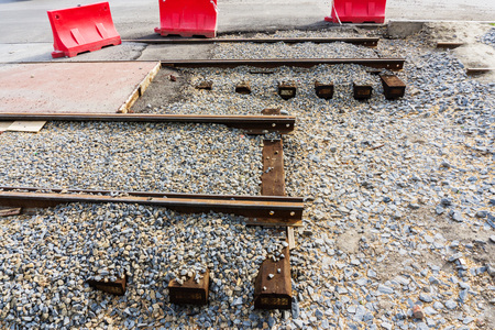 Laying of new steel rails on wooden sleepers in a prepared mound of large crushed stone for new tram lines in the city center 写真素材