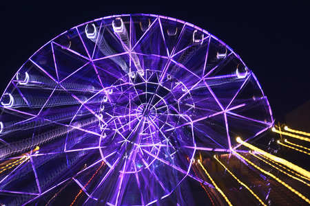 Lubricated when moving the camera on a long exposure illuminated by bright colors, the Ferris wheel in the park creates different varints of lines of light and colors for the background and patterns Stock Photo