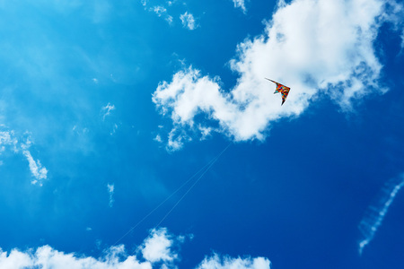 A large kite floats high in the sky among the clouds against the blue sky and the bright summer sun and it is controlled by two white ropes going to the ground