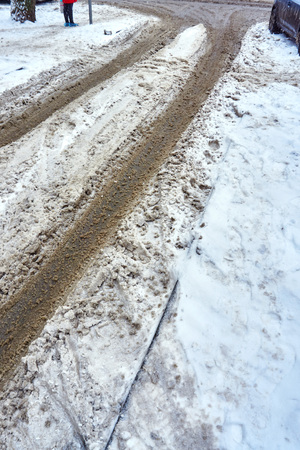A track on the roadway in the snow left by a car with dirty wheels in the sand