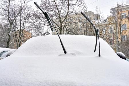 Kalte Winter in einem schneebedeckten Auto hoben vorsichtig die Scheibenwischer an, die nicht ins Glas gefallen wären