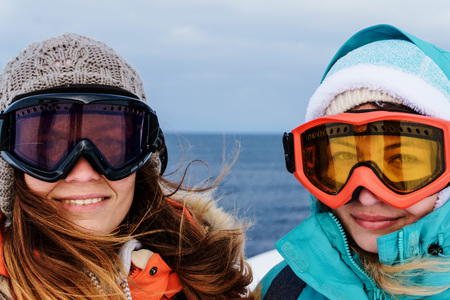 two girls friends dressed in bright warm jackets and hats during a hike along the northern coast of the Arctic Ocean on a frosty windy day in winter