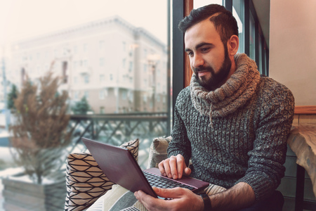 young guy with a beard in a sweater working behind a laptop in a warm cozy cafe