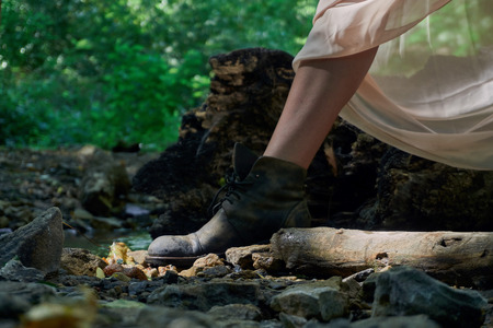 The legs of a young girl in a light summer dress and vintage shoes standing by a small stream on a clear sunny day in the forest. Through the thin dress the suns rays shine