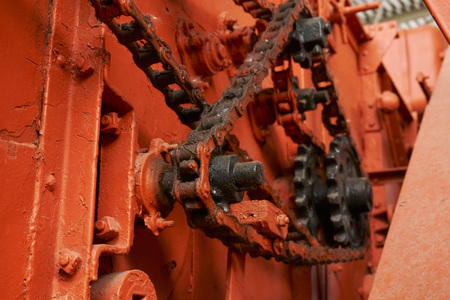 high-quality metal gears and chains on an old tractor of bright orange color in the museum of agricultural equipment Stok Fotoğraf
