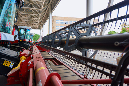 Devices for processing agricultural fields installed on a new combine of red and white colors in a large machinery plant