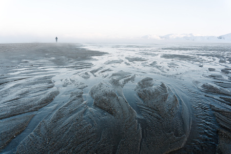 The outflow of water on the northern sea in winter shows the sand at the bottom that immediately freezes. lonely man stands far away on a drained bay