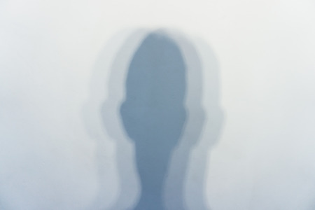 because of several light sources, a vague shadow from a human head on a white wall in a bright room Stock fotó