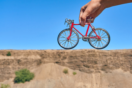 red metal toy bike in the hands against the background of a cliff in the distance with an optical illusion of a big bike on a clear sunny day in summer while traveling