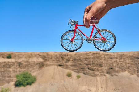 vélo jouet en métal rouge dans les mains sur fond de falaise au loin avec l'illusion d'optique d'un gros vélo par une journée ensoleillée en été en voyage