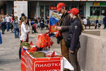 Rostov-on-Don  Russia - 9 May 2018: Street vendors on the tables in the middle of the street sell souvenirs, red flags, St. George ribbons and military symbolism in honor of the Victory Day holiday