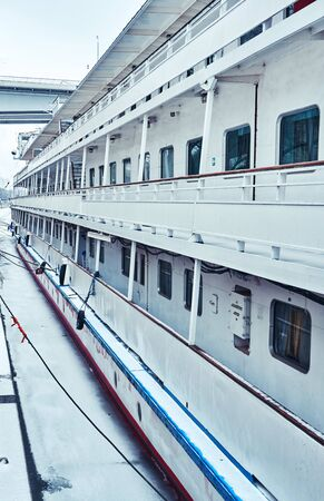Deck of a white blue moored passenger ship on the embankment with windows to the cabins and stairs