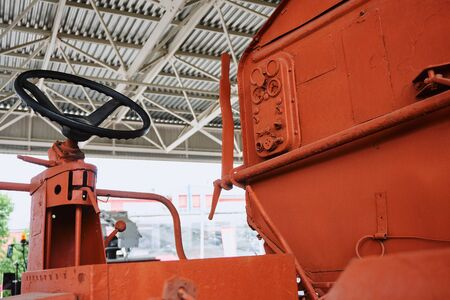 tractor operators workplace with steering wheel and levers on an old orange tractor without glazing under the open sky
