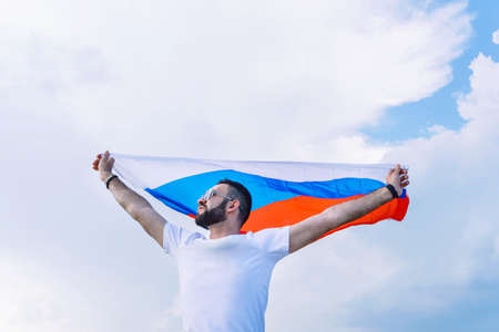 young guy in a white T-shirt with a stretched Russian flag against a blue sky on a hot day, fans for his sports team
