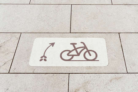 unusual tile showing the movement of a bicycle on a bicycle path laid on a new sidewalk fits in with the design and style of the new park