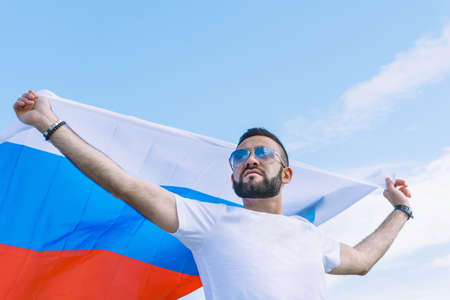 young guy in a white T-shirt with a stretched Russian flag against a blue sky on a hot day, fans for his sports team Banque d'images