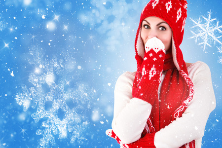 A young woman in a knitted hat, scarf and mittens .Red and white pattern.Beautiful, warm, knitted and crocheted items.Blue background, snowflakes.