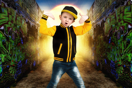 The little boy in the style of Hip-Hop. Childrens fashion.Cap and jacket. The Young Rapper.Graffiti on the walls.Cool rap dj.